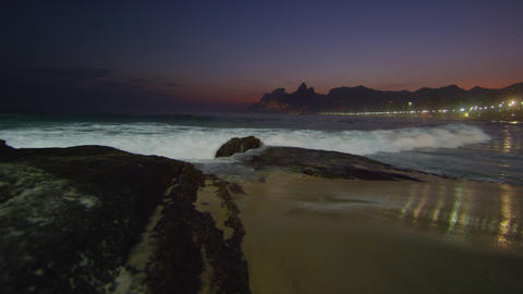 Slow motion tracking shot of the ocean flowing in against the Arpoador Rocks Footage