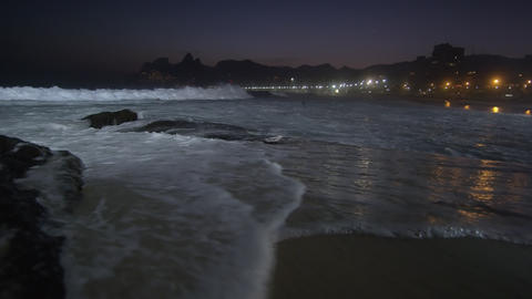 Slow motion, pan right as the tide flows up on Ipanema beach at night Footage