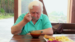 Elderly woman eats hot tomato soup Footage