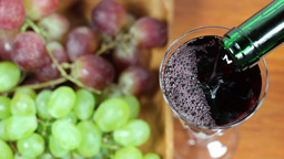 Red Wine Pouring Into A Glass. Grapes In Backgroun stock footage