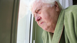 Elderly woman looking through the window 3 Footage