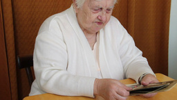 Elderly woman is watching her family old photos Footage
