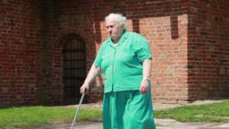 Senior woman walks with walking stick Footage