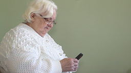 Old woman types short message on a mobile phone Footage