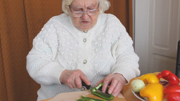 Old woman is slicing green pepper Footage