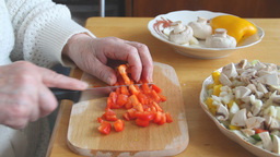 Old woman is slicing red pepper Footage