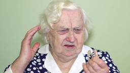 Old Woman Installing Hearing Aid stock footage