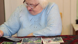 Elderly woman is watching own pictures. 2 Live Action