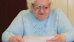 Senior woman is reading bad news in the letter Footage