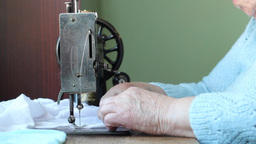 Old woman sews on the old sewing machine. 2 Live Action