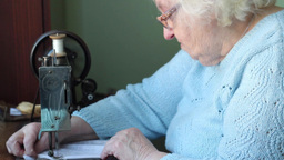 Old woman sews on the old Neuman sewing machine Live Action