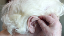 Hearing aid - old woman installing hearing aid Footage