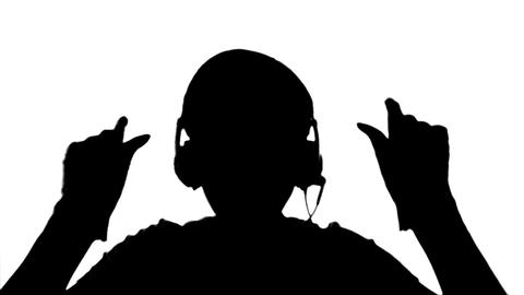 Silhouette of a girl listening to music on headpho Live Action