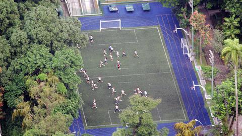 Bird's eye footage of people running across football field Footage