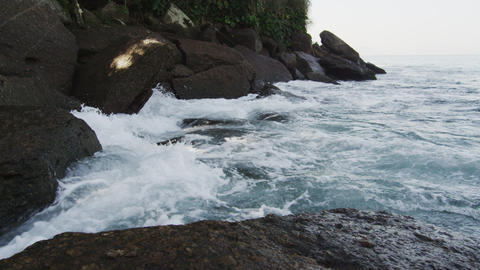 Tracking slow motion shot of heavy surf pounding on craggy boulders Footage