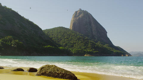 Slow motion shot of the beautiful Red Beach in Rio with waves washing over expos Footage