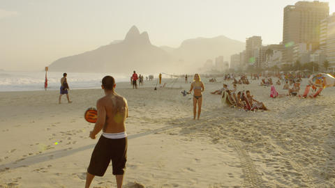 A couple playing tennis on Ipanema beach together Footage