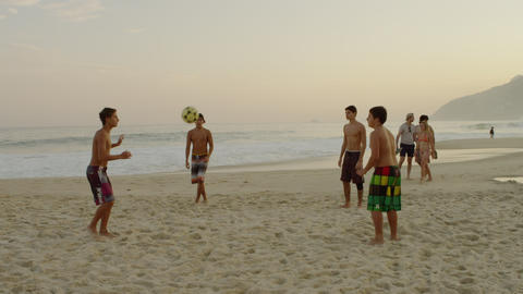 RIO DE JANEIRO-JUNE16: Teens kicking a football at the beach on June 16, 2013 in Footage