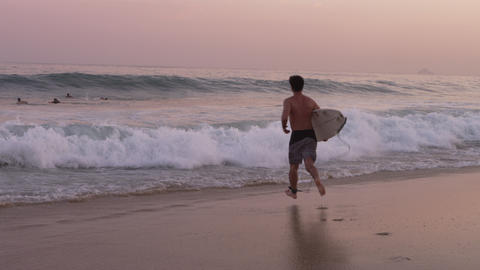 Male surfer running into the ocean, leaping onto his surfboard Footage