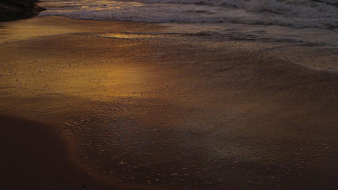 Slow motion, tilt up from ocean ripple to waves on Praia do Diabo (Devil's Beach Footage