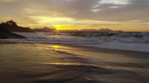 Slow motion, dolly out as waves crash against Ipanema beach at sunset Footage