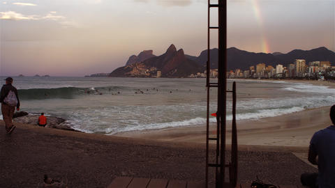 Camera pans to a rainbow in the distance at Ipanema Beach in Rio de Janeiro Footage