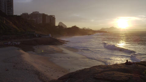 A camera pan of people in the distance on Ipanema Beach at sunset Footage