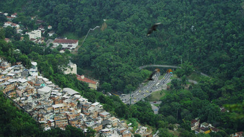Eagles fly over a city bluff overlooking a tunneled intersection in Rio de Janei Footage