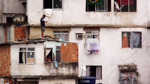 RIO DE JANEIRO, BRAZIL - JUNE 23: Man standing on roof and girl on balcony in Ri Footage