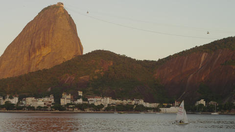 Static shot of a sailboat on Guanabara Bay with Sugarloaf Mountain in the distan Footage