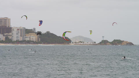 Panning shot from shore of parasailing surfers and cityscape Footage