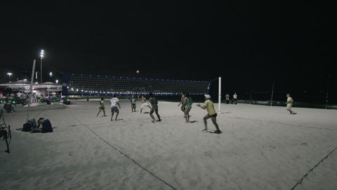 Static shot of volleyball player in yellow jersey and hat hitting volleyball and Footage