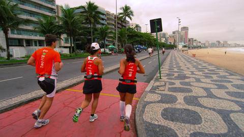 Slow tracking shot of three runners running along the street near Ipanema beach  Footage