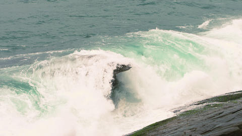 Slow motion shot of waves breaking on the rocks along Rio de Janeiro coastline i Footage