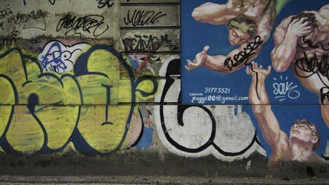 Slow motion tracking shot of various graffiti on walls along a street in Rio de  Footage