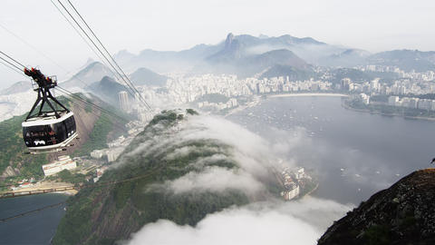 Pan of a gondola ride on a misty day over the Brazilian coastline in Rio de Jane Footage