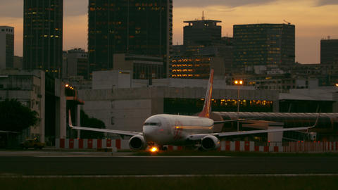 Static shot of plane taxiing down runway with Rio de Janeiro in the Background Footage