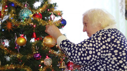 Elderly woman decorates christmas tree Footage