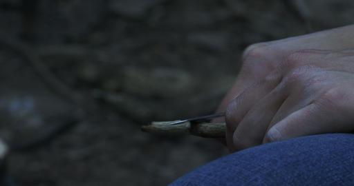 Woman sharpening stick during camping Footage