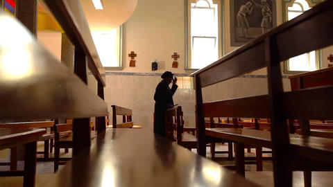 woman standing between pews and praying in Santiag Footage
