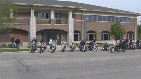 Motorcycle group parked on street pan Footage