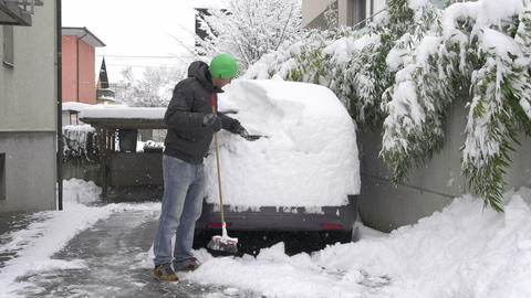 Man cleaning snow off his car Footage