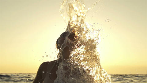 SLOW MOTION: Woman in the sea splashes her hair ba Footage