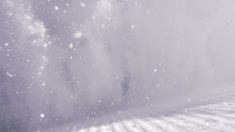SLOW MOTION: Snowboarder girl sprays snow into the Footage