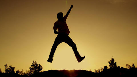 SLOW MOTION: young man jumping at sunset Footage