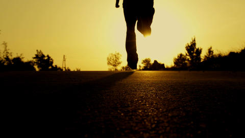 SLOW MOTION: man running at sunset Footage