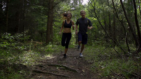 SLOW MOTION: A young couple jogging in the forest Footage