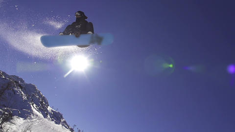 SLOW MOTION: Snowboarder jumping over the sun Footage