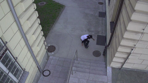 AERIAL SLOW MOTION: Skateboarder jumps over the st Footage