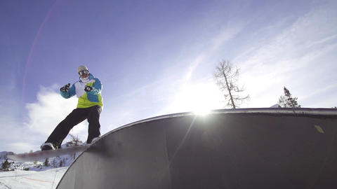 SLOW MOTION: Snowboarder rides a rainbow box Footage